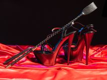 Adult sex games. Kinky lifestyle. Spank and a pair of black high-heeled shoes on the red linen. Bdsm outfit stock image