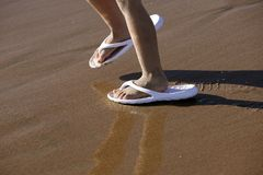Adult shoes for children feet on beach sand Royalty Free Stock Photos