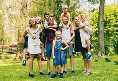 Adult siblings with little sisters and brothers. Portrait of happy adult siblings with little sisters and brothers sitting piggyback, looking at camera and Stock Photo