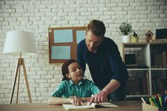 Adult single father helps to do homework to small royalty free stock photos