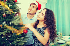 Adult smiling couple decorating Christmas tree. Adult  smiling couple decorating Christmas tree in home interior Stock Images