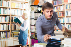 Adult smiling man choosing new book from many Royalty Free Stock Image
