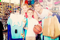 Adult smiling parents with boy in sport store Royalty Free Stock Photos