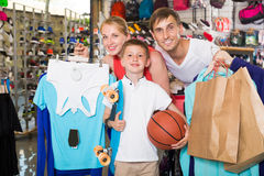Adult smiling parents with boy in sport store. Adult smiling parents with boy in school age shopping clothing in sport store Royalty Free Stock Photo