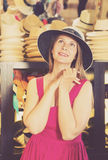 Adult smiling woman try on boater hat  in shopping mall Royalty Free Stock Photography