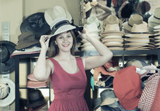 Adult smiling woman try on boater hat  in shopping mall Stock Photos