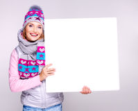 Adult smiling  woman in winter hat holds the white banner Royalty Free Stock Photos