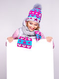 Adult smiling  woman in winter hat holds the white banner Royalty Free Stock Photo
