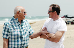 Adult son and father. Walking together on the beach royalty free stock photos