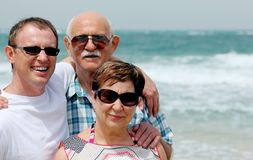 Adult son with his parents. Walking on the beach Stock Photos