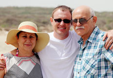 Adult son with his parents. Walking on the beach Royalty Free Stock Photo