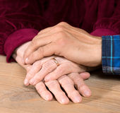 Adult son holding mothers senior hands at home Royalty Free Stock Photos