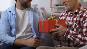 Adult son making present to father, hugging him, warm family relationships