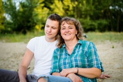 Adult son relaxing with his mother beside him Royalty Free Stock Image