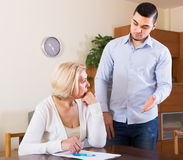 Adult son and senior mother with papers. Financial crisis in family of depressed adult son and his sad elderly mother Stock Image