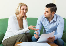 Adult son and senior mother with papers. Adult son and his upset mature mother with financial documents at home stock photo