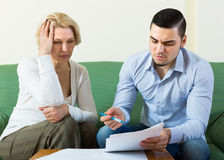Adult son and senior mother with papers. Sad adult son and his upset senior mother with financial documents at home. Focus on guy stock images