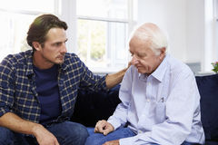 Adult Son Talking To Depressed Father At Home Stock Image