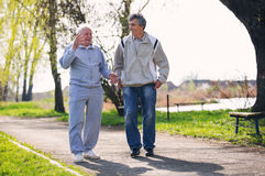 Adult son walking with his senior father royalty free stock photo