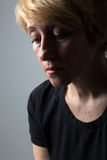 Adult sorrow woman. Sad blond woman in black clothes studio portrait Stock Image