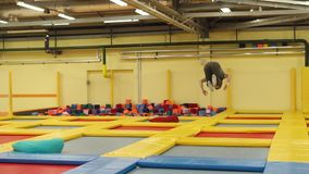 Jumper is training on bouncers in a gymnastic hall, jumping and whirling stock video footage