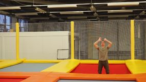 Adult sportsman is jumping on a trampoline in a gymnastic hall