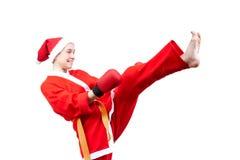 Adult sportswoman in dressed as Santa Claus hits a kick leg Royalty Free Stock Photo