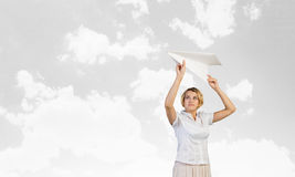 She is adult but still feeling playful. Young cheerful pretty woman playing with paper plane Stock Photo