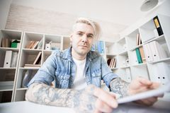 Adult student in classroom. Low angle view of Caucasian adult student with tattoos, dyed hair and earrings sitting in study room and looking at camera Stock Images