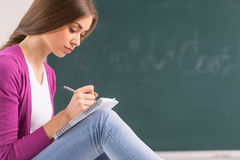 Adult student girl sitting and writing. Stock Images