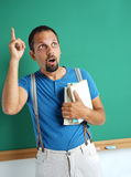 Adult student holding books in his hand and finger pointing up. Royalty Free Stock Images