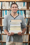 Adult student posing holding a stack of books. Smiling at camera Royalty Free Stock Photo