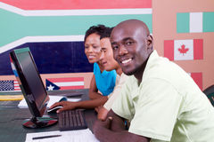 Adult students. Three adult students using computer together in a classroom Royalty Free Stock Photography