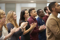 Adult students applauding at an event in their university Stock Image