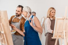 Adult students in aprons painting on easels during art. Class stock photo