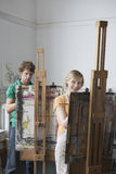 Adult Students In Art Class. Two adult students painting at easels in art class Stock Photography