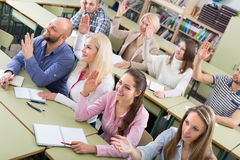 Adult students with hands up at class Royalty Free Stock Photos