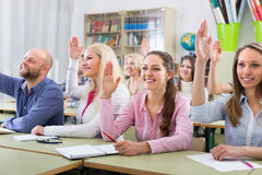 Adult students with hands up at class royalty free stock photography