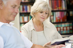 Adult students reading in a library.  Royalty Free Stock Photos