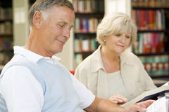 Adult students reading in a library Stock Photos