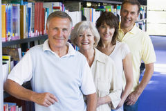 Adult students standing in a library Royalty Free Stock Images
