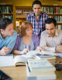 Adult students studying together in the library Stock Photography