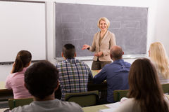 Adult students with teacher in classroom. Attentive adult students with smiling female teacher in classroom royalty free stock photography