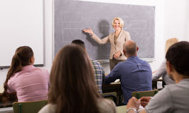 Adult students with teacher in classroom royalty free stock image