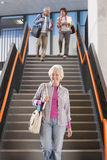 Adult students walking down stairs in college arriving for evening classes royalty free stock images
