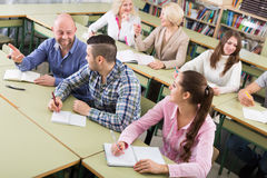 Adult students writing in classroom Stock Photos