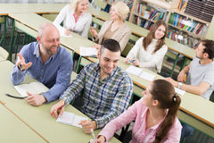 Adult students writing in classroom. Attentive adult students industriously writing down summary in the classroom Stock Photography