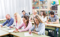 Adult students writing in classroom. Attentive adult students industriously writing down the summary in classroom Stock Image