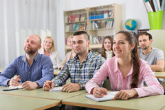 Adult students writing in classroom Stock Images