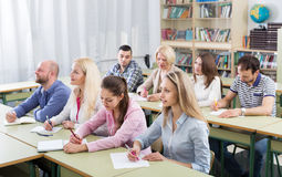 Adult students writing in classroom. Attentive adult students industriously writing down the summary in the classroom Royalty Free Stock Photos